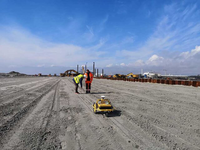 Aarsleff performing fast stakeout on sand for vertical drainage pipes using surveyor robot